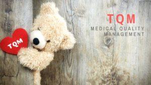 TQMと書かれたカードを持つ熊のぬいぐるみ
